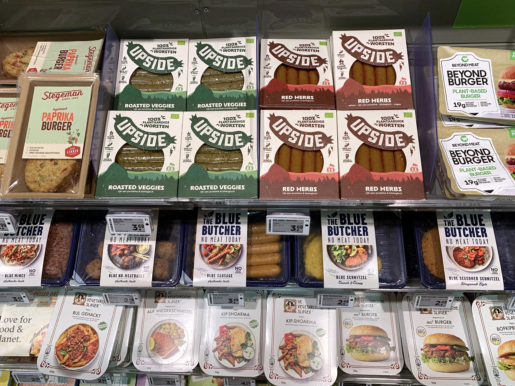 Verpakkingen van de plantaardige worsten van Upside in de winkelschappen van Plus Supermarkten